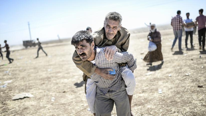 Ein Mann trägt einen älteren syrischen Kurden in der Nähe der türkisch-syrischen Grenze