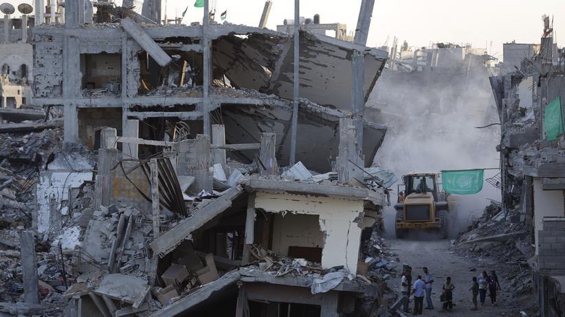 Palästinenser stehen vor ihren zerstörten Häusern in Gaza-Stadt.
