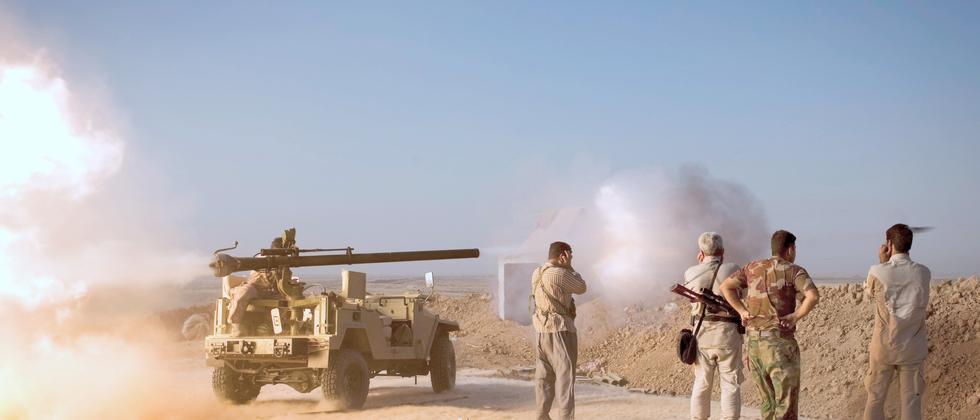 """Kurdische Peschmerga-Kämpfer aus dem Irak feuern in Richtung Truppen des """"Islamischen Staates"""" südlich der Stadt Kirkuk."""