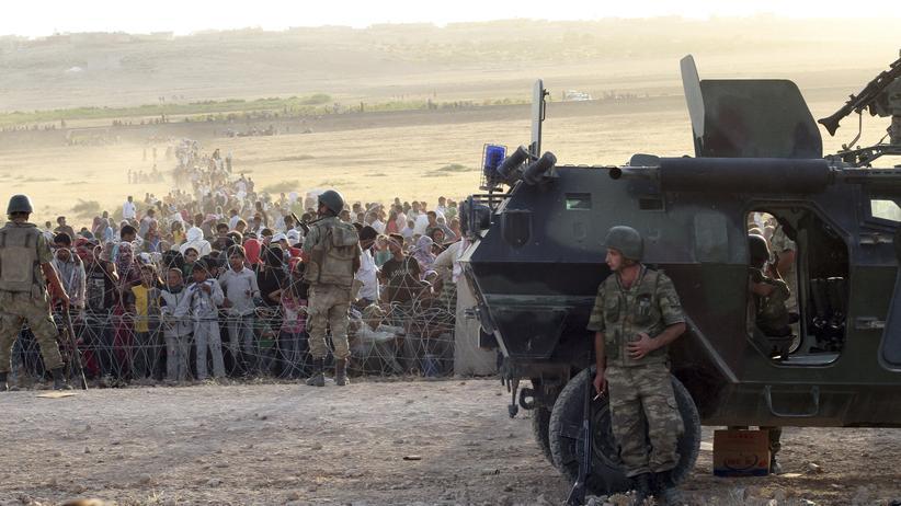 """""""Islamischer Staat"""": Türkische Soldaten bewachen die türkisch-syrische Grenze in der Nähe der Stadt Suruc, im Hintergrund warten syrische Flüchtlinge."""