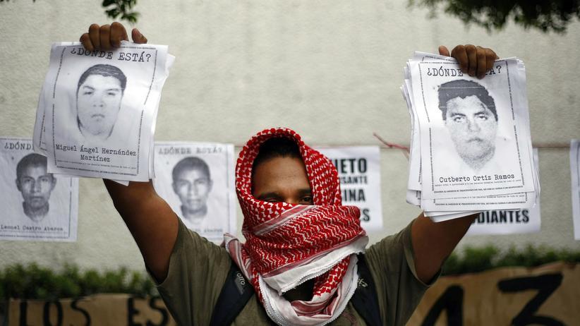 Mexiko: Ein Demonstrant mit Bildern der vermissten Studenten bei einer Protestveranstaltung vor der mexikanischen Botschaft in Guatemala