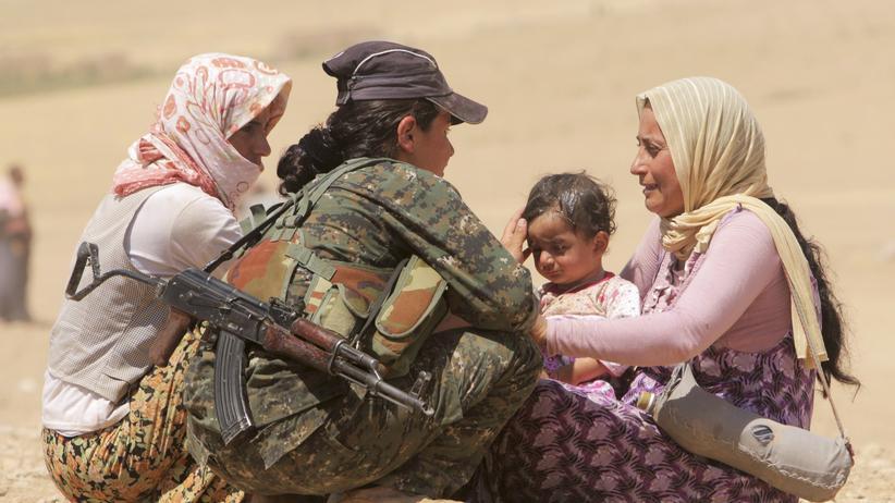 CIA-Bericht: Eine Kämpferin der Volksschutzeinheiten YPG spricht mit jesidischen Frauen an der syrischen Grenze.