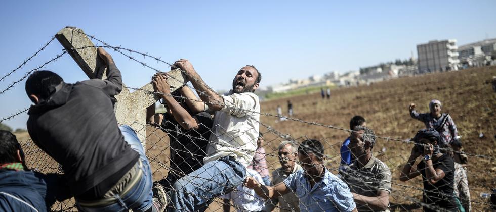 Aktivisten reißen einen Grenzzaun zwischen der Türkei und Syrien nieder.