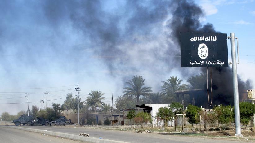 """""""Islamischer Staat"""": Kämpfe zwischen IS-Milizen und irakischen Sicherheitskräften nordöstlich von Bagdad. Im Vordergrund eine Flagge des """"Islamischen Staates"""""""