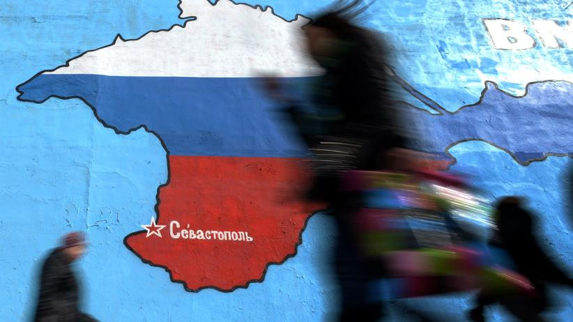 Ukraine-Krise: Pedestrians walk past an wall painting depicting a map of Crimean peninsula bearing the colours of Russia's national flag in Moscow, on March 31, 2014. The Crimean crisis has sparked the most explosive East-West confrontation since the Cold War and fanned fears in Kiev that Russian President Vladimir Putin now intends to push his troops into southeast Ukraine. AFP PHOTO / VASILY MAXIMOV (Photo credit should read VASILY MAXIMOV/AFP/Getty Images)