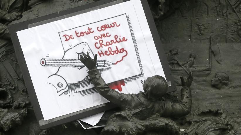 Terrorangriff in Paris: Eine Karikatur von Plantu an einer Statue auf der Place de la République in Paris