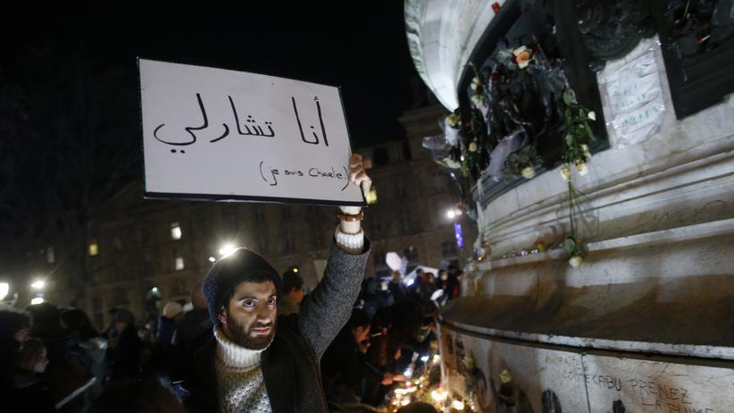 """""""Ich bin Charlie"""" steht auf Arabisch auf dem Plakat dieses Mannes in Paris"""