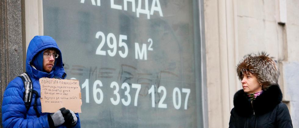 In der Moskauer Innenstadt bettelt ein Mann um Geld