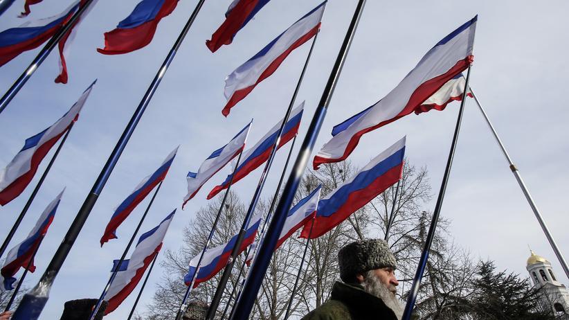 Amnesty International: Prorussische Mitglieder der sogenannten Selbstverteidigungstruppen zeigen anlässlich des Jahrestags der Krim-Annexion die Flaggen Russlands und der Krim.