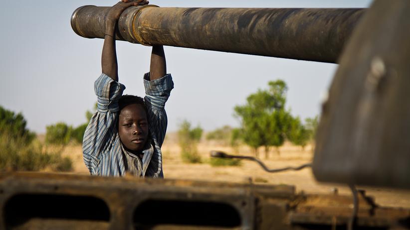 Sudan: Junger Sudanese und zerstörter Panzer