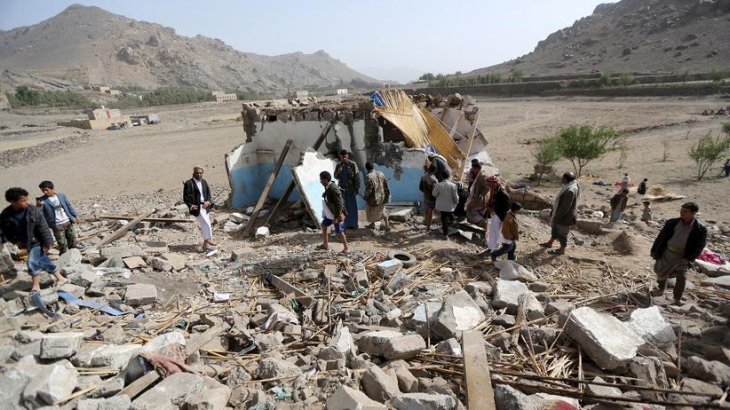 Menschen versammeln sich an einem zerstörten Haus in der Nähe von Sanaa.