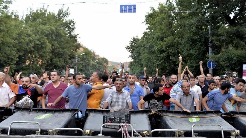 Protestierende hinter den Barrikaden aus Müllcontainern in Jerewan