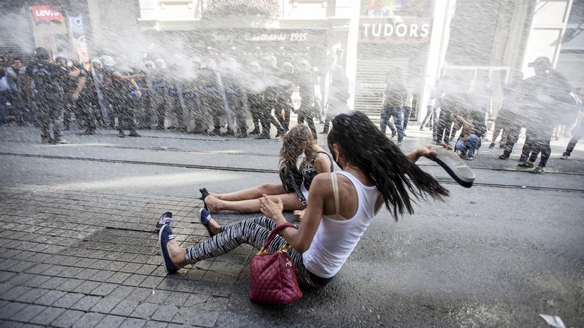 Istanbul: Zwei Frauen versuchen sich in Istanbul gegen den Angriff eines Wasserwerfers zu schützen.