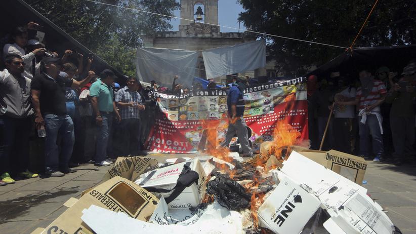 Mitglieder der radikalen Lehrergewerkschaft CNTE verbrennen Wahlunterlagen.