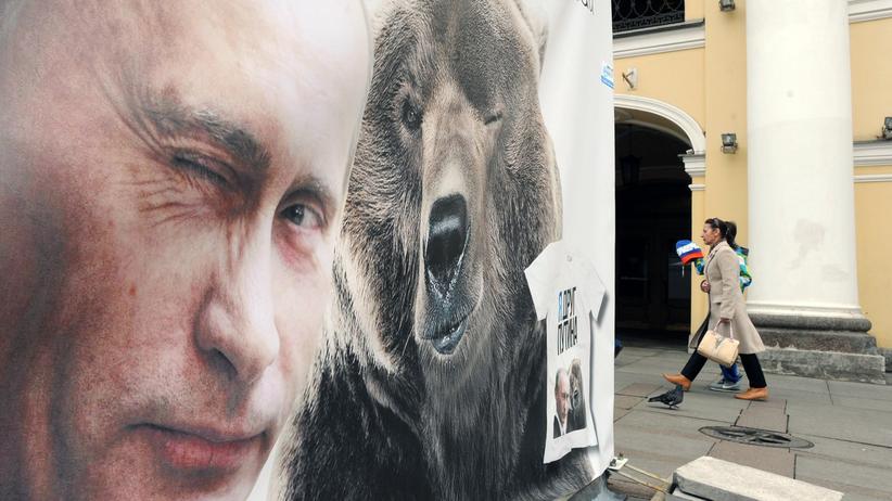 Russland: Ein Plakat mit dem russischen Präsidenten und einem Bären in Sankt Petersburg