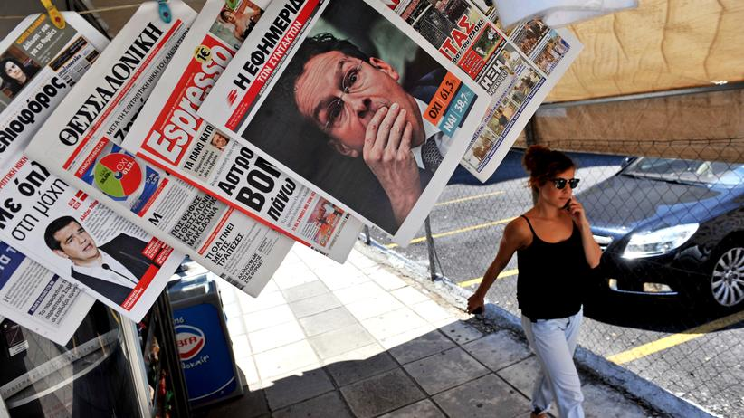 Referendum: A woman passes a newspaper kiosk with journal headlines showing the results of Greece's referendum, in Thessaloniki, on July 6, 2015. More than 61 percent of Greek voters rejected fresh austerity demands by the country's EU-IMF creditors in a historic referendum, official results from over 95 percent of polling stations showed. AFP PHOTO / SAKIS MITROLIDIS (Photo credit should read SAKIS MITROLIDIS/AFP/Getty Images)