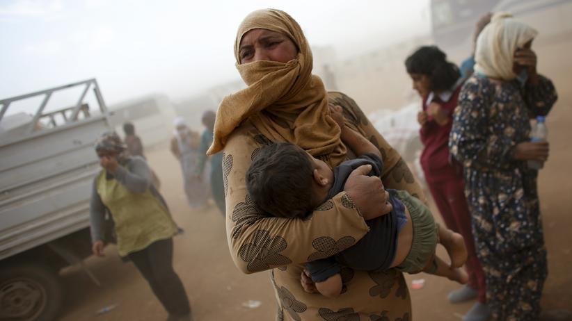 Syrien: Eine flüchtende Syrerin wartet mit ihrem Kind an der Grenze zur Türkei auf den Weitertransport.