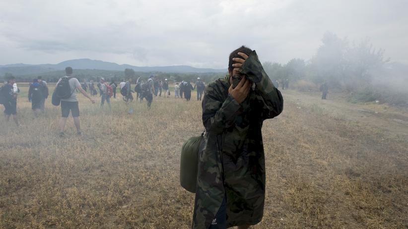 Mazedonien: Ein Mann bedeckt am Wochenende in der Nähe der mazedonisch-griechischen Grenze zum Schutz vor Tränengas sein Gesicht.