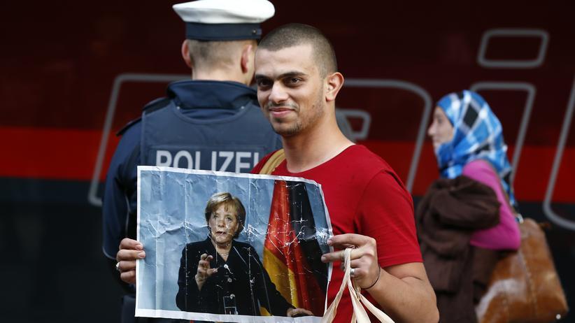 Angela Merkel: A refugee, arriving at Munich main station, carries a portrait of German chancellor Angela Merkel.