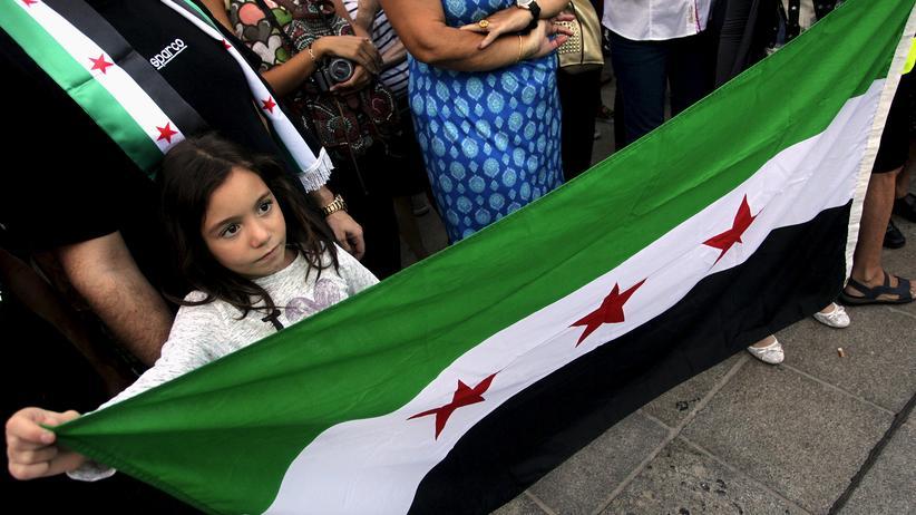 Ein Mädchen hält bei einem Protestzug für mehr Flüchtlingshilfe im spanischen Valencia die syrische Flagge