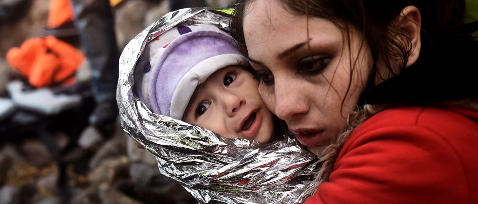 Eine Frau mit einem Baby in einem Aufnahmelager auf Lesbos, Griechenland