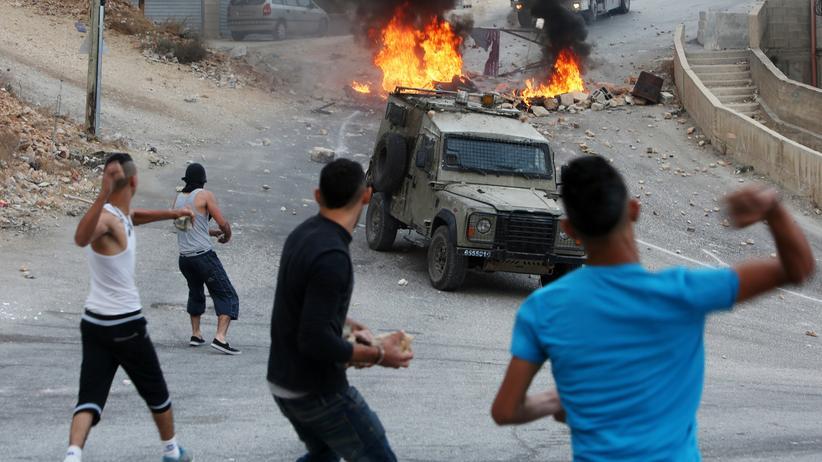 Palästinenser werden in der Stadt Nablus Steine auf Fahrzeuge israelischer Sicherheitskräfte.