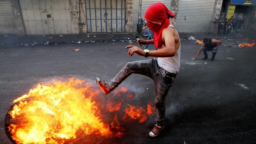 Nahost-Konflikt: Ein Palästinenser tritt während Auseinandersetzungen zwischen israelischen Sicherheitskräften und Palästinensern in Hebron gegen einen brennenden Reifen.