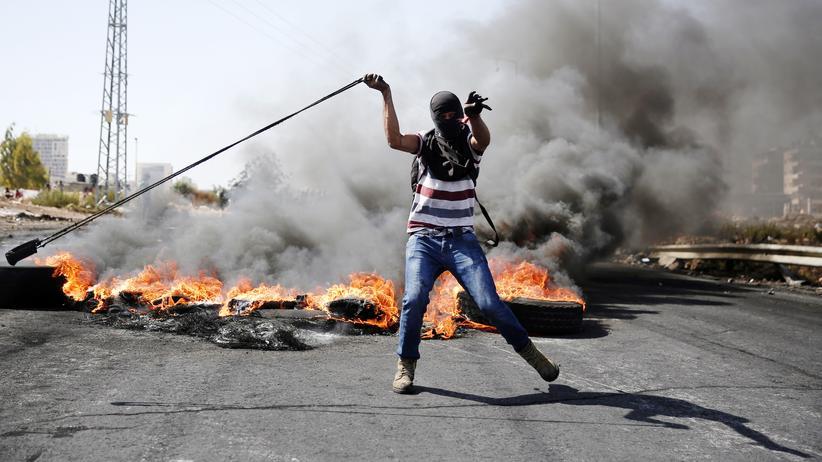 Palästina: Ein palästinensischer Demonstrant wirft im Westjordanland Steine auf israelische Sicherheitsleute