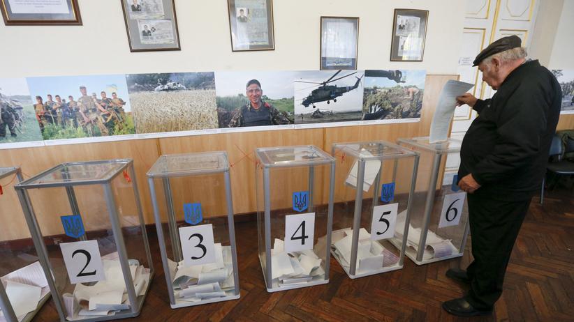 Ukraine: In Kiew gibt ein Mann seinen Wahlzettel zu den Regionalwahlen ab.