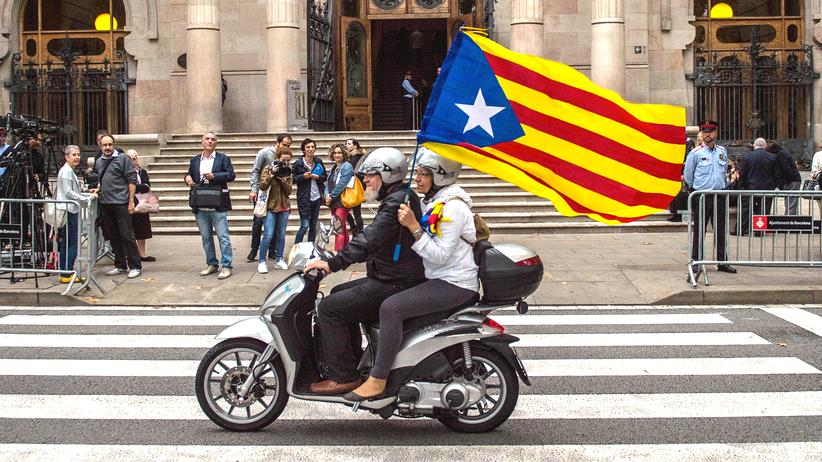 Spanien: Befürworter der katalanischen Unabhängigkeit fahren mit einer Katalonien-Flagge durch Barcelona.