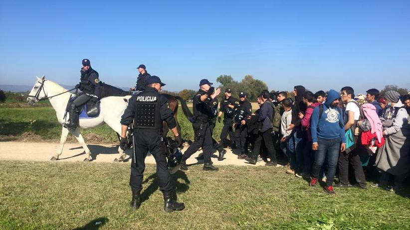 Polizisten versuchen, die Flüchtlingskarawane zu lenken.