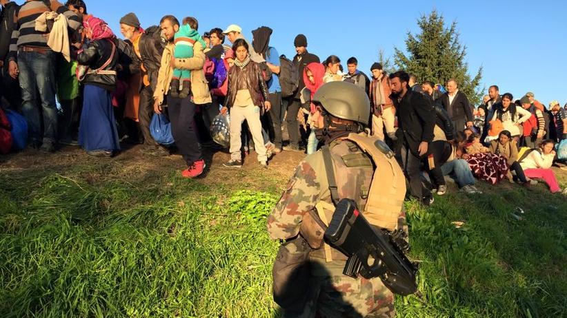 Bewacht von einem Soldaten, warten die Flüchtlinge auf einem Deich.