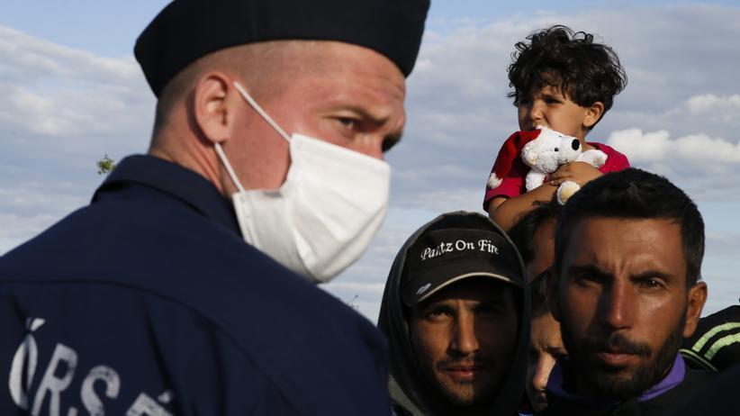 Ein ungarischer Polizist vor einer Gruppe Migranten am serbisch-ungarischen Grenzübergang Röszke