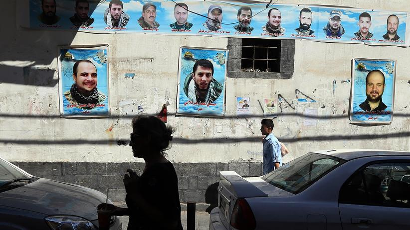Baschar al-Assad: Syrians walk past portraits of pro-government forces members killed in combat, on September 21, 2015, in the capital Damascus. AFP PHOTO / JOSEPH EID (Photo credit should read JOSEPH EID/AFP/Getty Images)