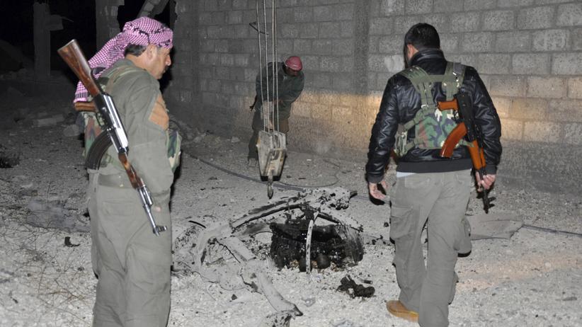 Kämpfer in Syrien inspizieren die Schäden nach einem Selbstmordanschlag. (Archiv)
