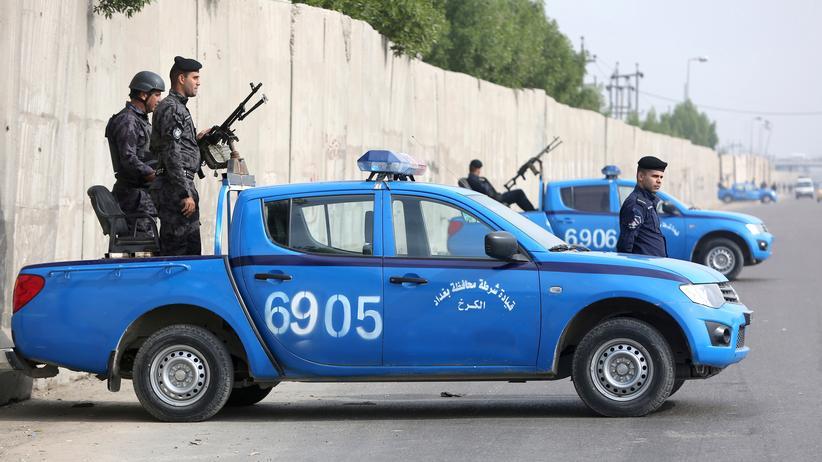Irakische Polizisten bewachen eine Hauptstraße in Bagdad