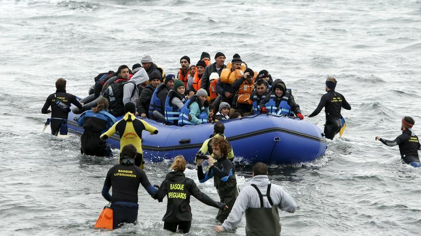 Syrienkrieg: Freiwillige waten auf ein Schlauchboot mit Flüchtlingen zu, das am 29. Januar 2016 auf der griechischen Insel Lesbos ankommt.