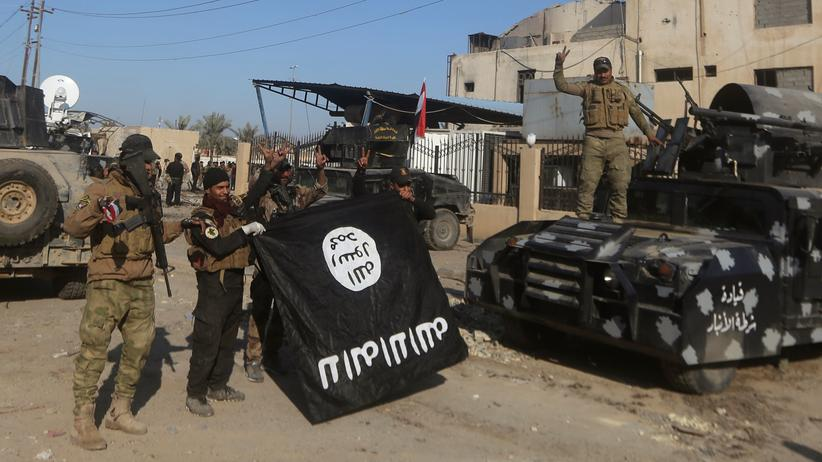 """Syrienkrieg: Mitglieder der irakischen Anti-Terror-Einheit mit der Flagge des """"Islamischen Staates"""", nach der Rückeroberung von Ramadi Ende Dezember 2015"""