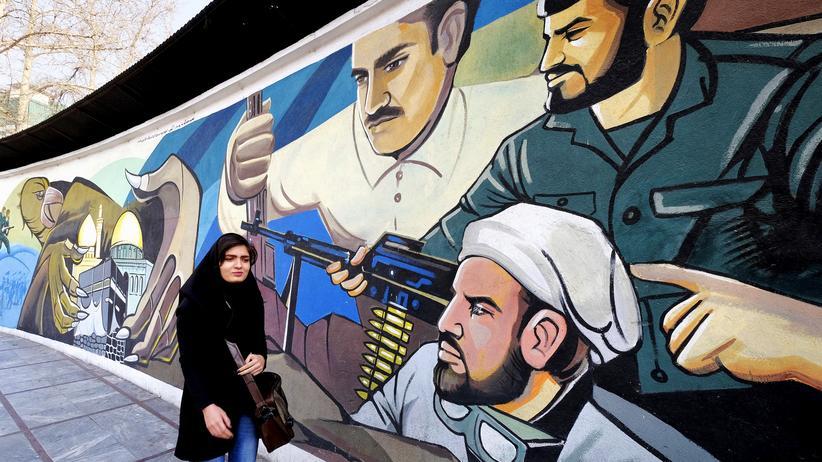 Iran: Eine junge Iranerin läuft an einem Mural in Teheran vorbei, das die Revolutionsgarde zeigt.