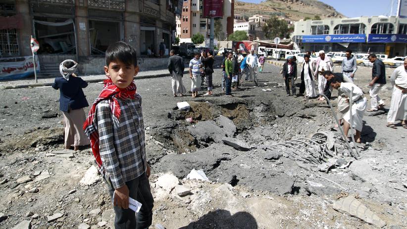 Jemen: Nach Luftanschlägen begutachten Passanten einen Krater in Jemens Hauptstadt Sanaa.