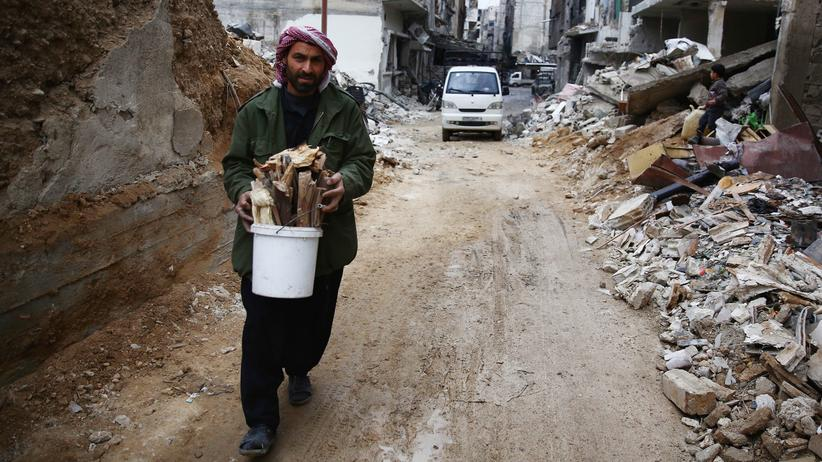 Syria: A man collects firewood from the rubble of destroyed buildings in the rebel-held town of Douma, on the eastern edges of the Syrian capital Damascus.