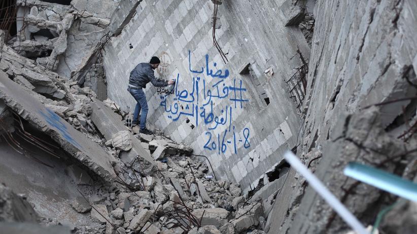 Ein syrischer Aktivist sprayt ein Graffiti an ein Gebäude in Damaskus, mit dem er seine Solidarität mit der von Assads Armee besetzten Stadt Madaja kundtut, in der bereits Menschen verhungern.
