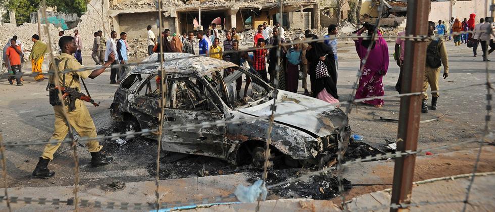 Zivilisten stehen vor einem gesprengten Auto nach der Attacke auf ein Hotel in Somalia.