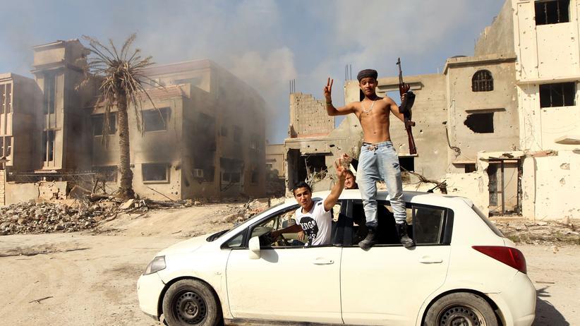 Kämpfer der libyschen Regierung feiern nach dem Sieg gegen die islamistischen Milizen in der Stadt Bengasi.