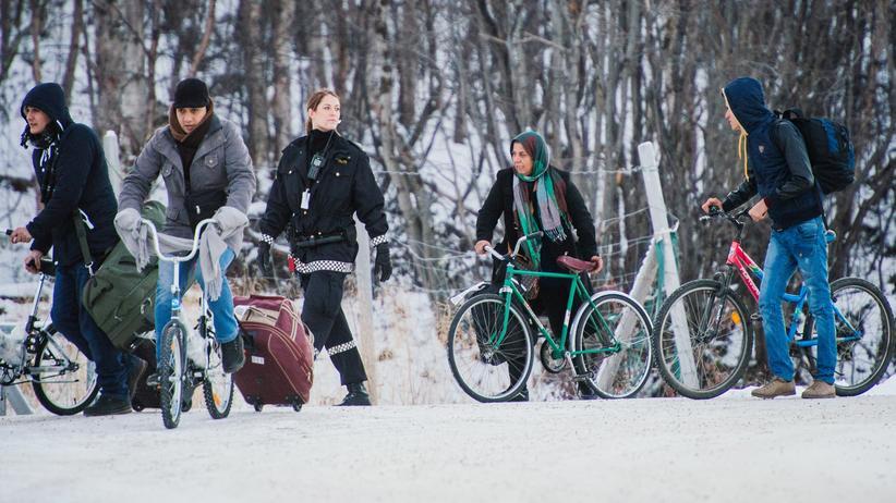 Russland: Route nach Europa: Flüchtlinge fahren im mit ihren Rädern durch den Schnee zur russisch-norwegischen Grenze.