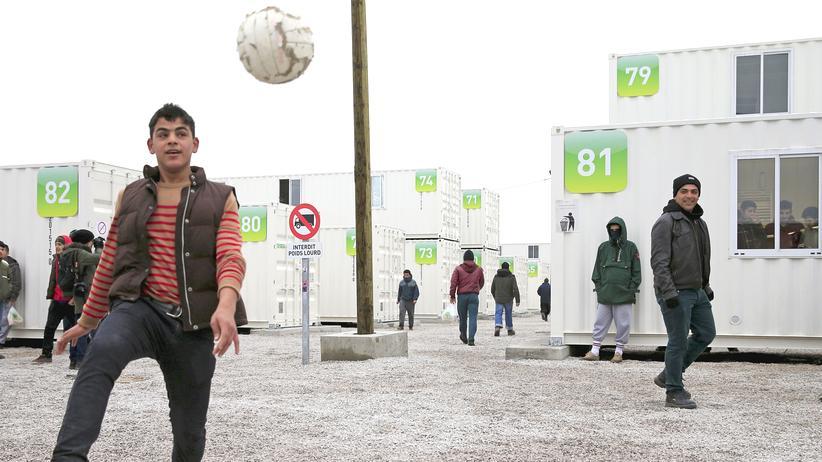 Ein Junge spielt Fußball vor Containerhäusern in der Nähe von Calais, Frankreich