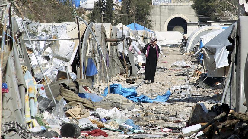 Syrienkonflikt: Eine Frau geht durch die Trümmer eines Lagers für syrische Flüchtlinge an der Grenze zur Türkei. Das Lager wurde nach Angaben der Bewohner durch Beschuss einer mit dem Assad-Regime verbündeten Miliz getroffen.