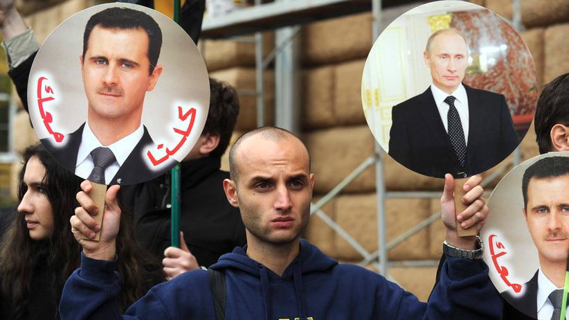 Syrien-Konflikt: Ein Demonstrant hält in Moskau zwei von acht Kriegsherren, die in Syrien ihre Ziele verfolgen, anklagend in die Höhe.