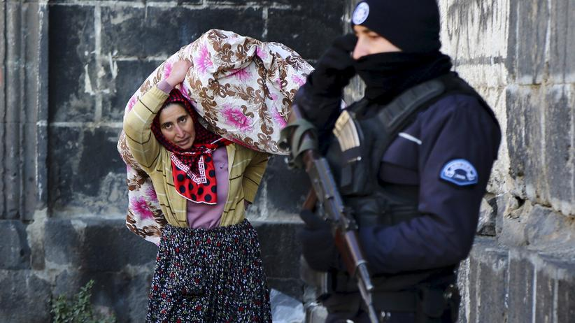 Syrien: A resident carries her belongings past a police officer as she flees from Sur district, which is partially under curfew, in the Kurdish-dominated southeastern city of Diyarbakir, Turkey January 27, 2016. Security forces killed 20 Kurdish militants in southeast Turkey while three Turkish soldiers died in a rebel attack, the military said on Wednesday, as authorities widened a curfew in the mainly Kurdish region's largest city, Diyarbakir.