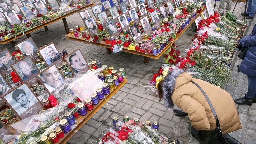 Ukraine: Am 20. Februar 2016, dem zweiten Jahrestag der Euromaidan-Revolution, legt eine Ukrainerin Blumen auf dem Maidan in Kiew ab.